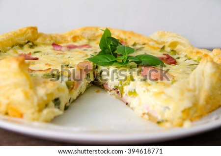 Homemade Spinach and Bacon Egg Quiche in a pie crust cut piece on plate. French cuisine - stock photo