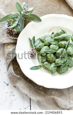 homemade spinach dumplings with sage leafs and flowers on plate on rustic background with burlap on wooden table