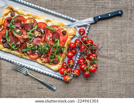Homemade square pizza with meat, salami, cherry-tomatoes and fresh arugula on a silver tray over a sackcloth background - stock photo