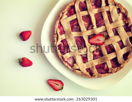Homemade  strawberry and rhubarb pie on the white table. Retro toned photo, top view - stock photo