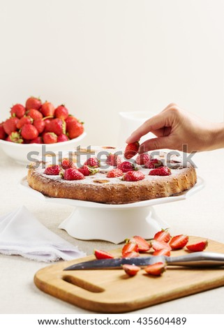Homemade strawberry cake on a white cake stand. Selective focus. - stock photo