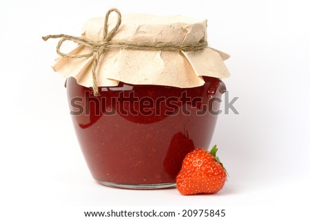 Homemade strawberry jam in a jar covered with paper, and one strawberry aside. - stock photo