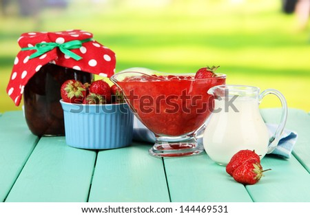 Homemade strawberry jam, on color wooden table, on bright background - stock photo
