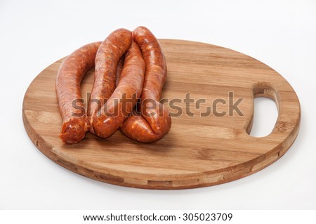 Homemade stuffed sausage on the round wooden board. - stock photo