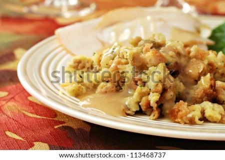 Homemade stuffing with gravy served on dinner plate (with turkey in background) on seasonal tablecloth for Thanksgiving.  Closeup with shallow dof.