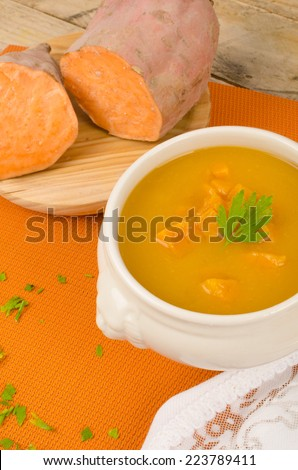 Homemade sweet potato soup with its main ingredient next to it - stock photo