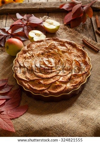 Homemade sweet traditional apple pastry cake for holiday celebration with cinnamon and apples on vintage wooden background. Autumn decor. Rustic style and natural light. - stock photo