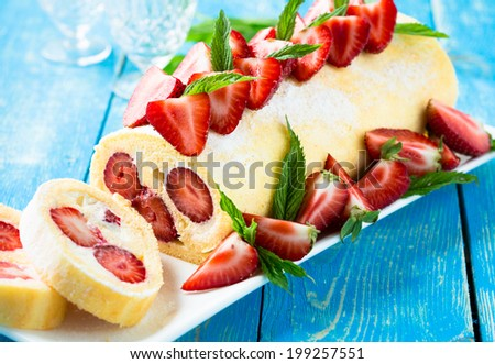 Homemade swiss roll biscuit cake with strawberries - stock photo