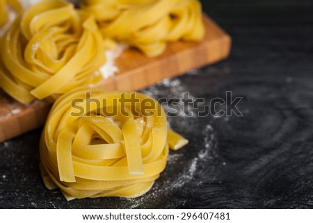 Homemade tagliatelle. Raw pasta on the wooden table. Selective focus. - stock photo