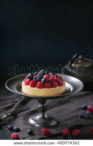 Homemade tart with custard, fresh raspberries and blueberries, served on vintage metal plate with iron teapot on textile napkin over old wooden table. Dark rustic style - stock photo