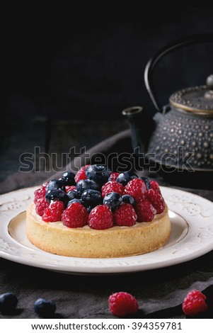 Homemade tart with custard, fresh raspberries and blueberries, served on white vintage plate with iron teapot on textile napkin over old wooden table. Dark rustic style - stock photo