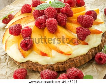 Homemade tart with nectarine, raspberries and custard. Shallow dof. - stock photo