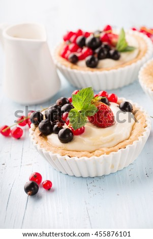 Homemade Tartlets with cream and fresh berries - ripe red and black currants, strawberries on blue rustic wooden table, selective focus