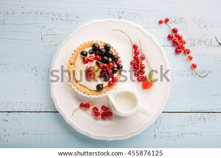 Homemade Tartlets with cream and fresh berries - ripe red and black currants, strawberries on blue rustic wooden background, top view - stock photo