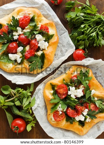Homemade tarts with cottage cheese, herbs and cherry tomatoes. Viewed from above. - stock photo