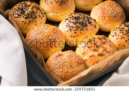 Homemade tasty buns with sesame and cumin on tray - stock photo