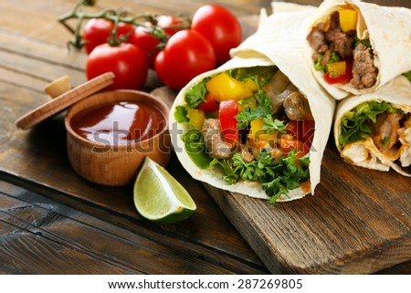 Homemade tasty burritos with vegetables, potato chips on cutting board, on wooden background - stock photo