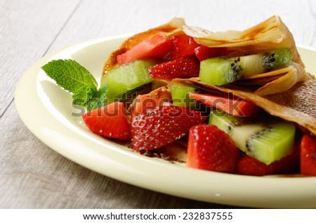Homemade tasty crepes with strawberries and kiwi