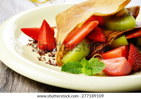 Homemade tasty crepes with strawberries and kiwi - stock photo