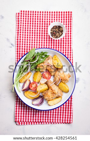 Homemade tasty roasted chicken wings with roasted potato with vegetables in an enamel bowl, top view - stock photo