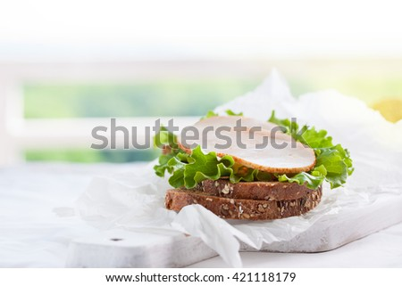 Homemade tasty sandwich with salad leaves and ham on a cutting board on a kitchen background, horizontal with place for text - stock photo