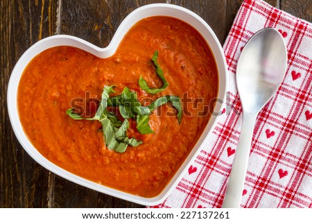 Homemade tomato and basil soup in white heart shaped bowl with spoon and red heart napkin - stock photo