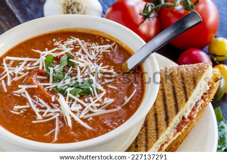 Homemade tomato and basil soup sprinkled with parmesan cheese in white round bowl with spoon and grilled cheese panini sandwich - stock photo