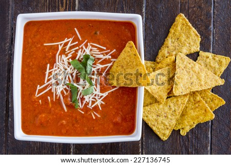 Homemade tomato and basil soup sprinkled with parmesan cheese in white square bowl and pumpkin tortilla chips - stock photo