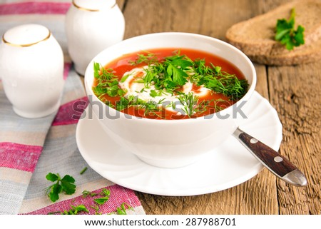 Homemade tomato cold soup with cream cheese and fresh herbs on rustic wooden table