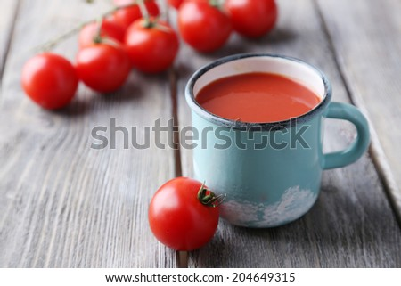 Homemade tomato juice in color mug and fresh tomatoes on wooden background - stock photo
