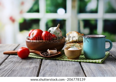 Homemade tomato juice in color mug, bread sticks, spices and fresh tomatoes on wooden table, on bright - stock photo
