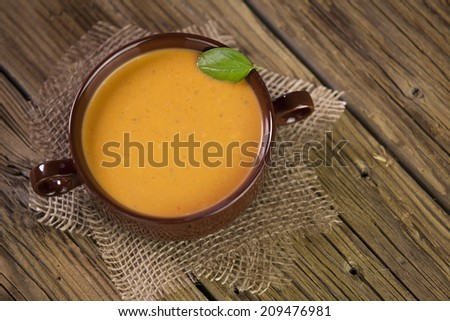 homemade tomato soup with basil leaf on top - stock photo