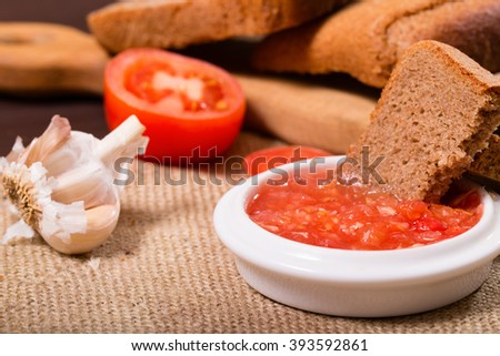 Homemade tomatoes sauce on a sacking. Against from pieces of rye bread and garlic in rural style. Close up, small depth of sharpness - stock photo