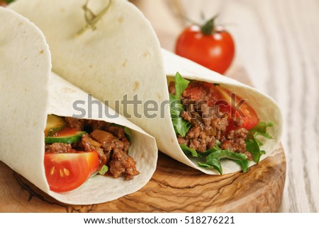 homemade tortilla with beef, frillice and vegetables on wooden board