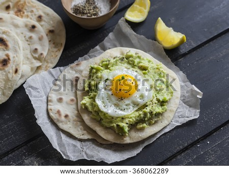 Homemade tortilla with mashed avocado and a fried quail egg. Delicious snack, healthy food - stock photo