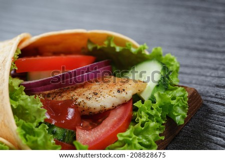 homemade tortillas with chicken and vegetables, on wood table - stock photo