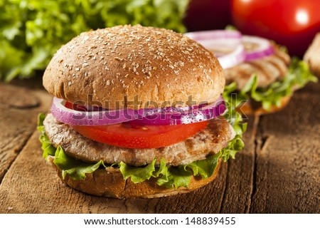Homemade Turkey Burger on a Bun with Lettuce and Tomato - stock photo