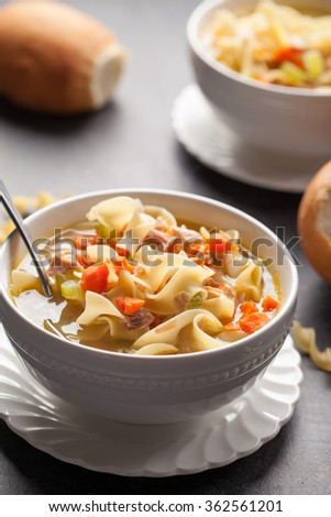 Homemade Turkey Noodle Soup with piping hot rolls macro side shot