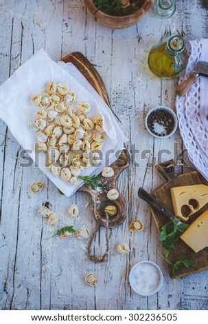 Homemade uncooked ravioli and parmesan cheese over on vintage wooden board above from white wooden rustic table with olive oil and green leaves. Rustic style  - stock photo