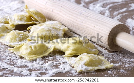 homemade uncooked ravioli with a roller on wooden table - stock photo