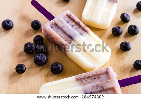 Homemade vanilla, blueberry and coconut milk popsicles sitting on wooden table with fresh berries