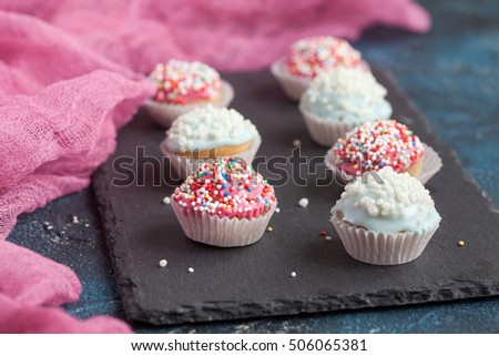 Homemade vanilla cupcakes with with chocolate icing cup and sprinkles on a dark background. Selective focus and space for text.