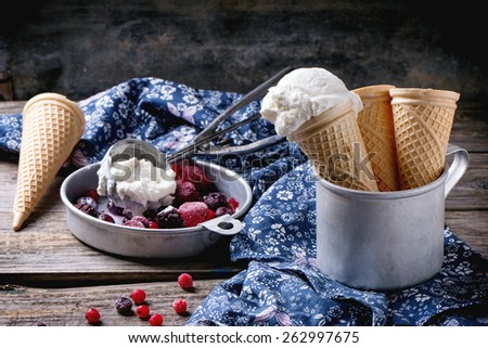 Homemade vanilla ice cream in wafer cones and empty waffer cones, served in metal bowl with frozen berries and spoon over wooden table with blue textile - stock photo