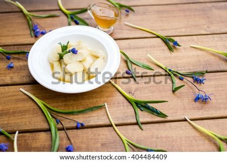 Homemade vareniki with ingredients on wood background - stock photo