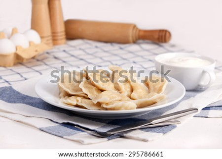 Homemade varenyky Ukrainian traditional dish. Perogy, stuffed dumplings served on white plate. Ukrainian cuisine. Background with food and decorations. - stock photo