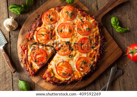 Homemade Vegan Cauliflower Crust Pizza with Tomato and Basil - stock photo
