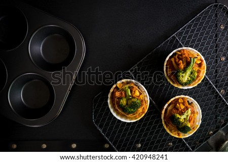Homemade vegan muffins with tomatoes and broccoli on black background with muffin tray and metal grille - stock photo
