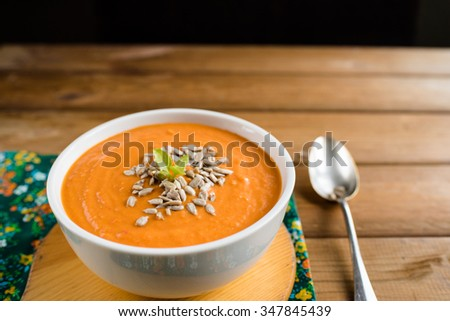 Homemade vegan tomato soup with sunflower seeds in a white bowl on a brown, wooden table - stock photo