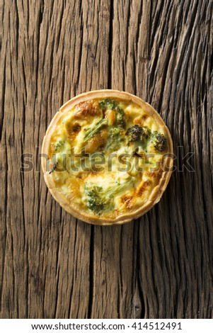 Homemade vegetable quiche. The food is sitting on a rustic wooden background. - stock photo