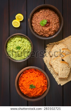 Homemade vegetable spreads (red kidney bean, zucchini and parsley, carrot and red bell pepper), slices of wholegrain bread and lemon on the side, photographed overhead on dark wood with natural light